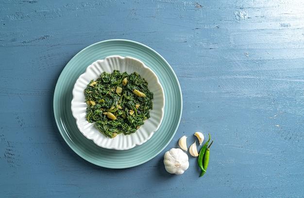 Keto dieta alimentare spinaci curry in ciotola bianca e piatto blu con aglio e peperoncini su tavolo in legno blu vista dall'alto