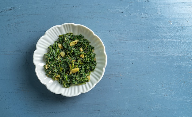 Keto dieta alimentare spinaci curry in ciotola bianca sulla vista del piano d'appoggio in legno blu