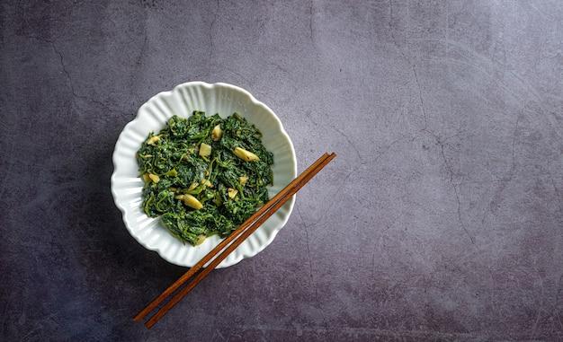 Keto diet food spinaci curry in una ciotola bianca con bacchette su piastrelle di ardesia nera vista dall'alto
