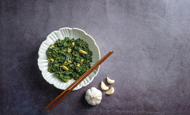 Keto diet food spinaci curry in una ciotola bianca con bacchette e aglio su piastrelle di ardesia nera vista dall'alto