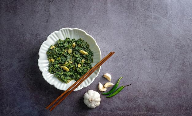 Cibo dietetico keto curry di spinaci in una ciotola bianca con peperoncini all'aglio bacchette su piastrelle di ardesia nera vista dall'alto black