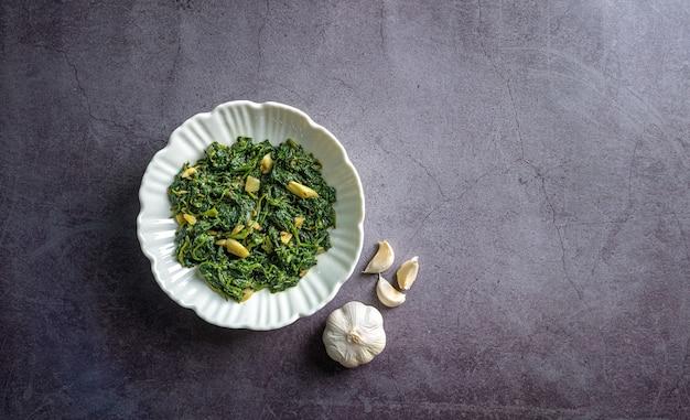 Keto diet food spinaci curry in una ciotola bianca con aglio su piastrelle di ardesia nera vista dall'alto