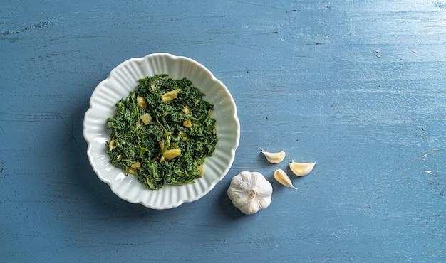 Keto dieta alimentare spinaci curry in ciotola bianca con aglio su tavolo in legno blu vista dall'alto