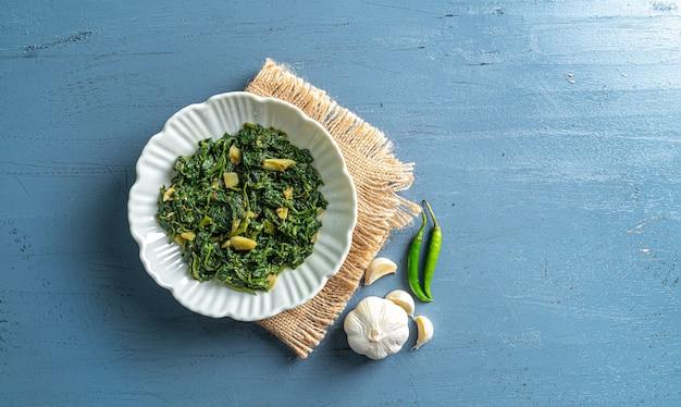 Keto dieta alimentare spinaci curry in ciotola bianca con peperoncini all'aglio con strato vintage su tavolo in legno blu vista dall'alto
