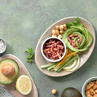 Dieta cheto, vista dall'alto di rosa avocado insalata con cubetti di pancetta e formaggio affumicato sul tavolo verde