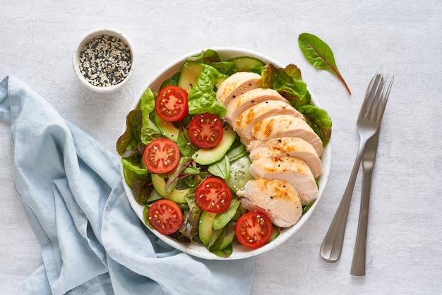 Insalata di keto con carne di pollo sous vide, pomodori, cetrioli, avocado su tovaglia di lino pastello. cucina mediterranea, dieta chetogenica a basso contenuto calorico