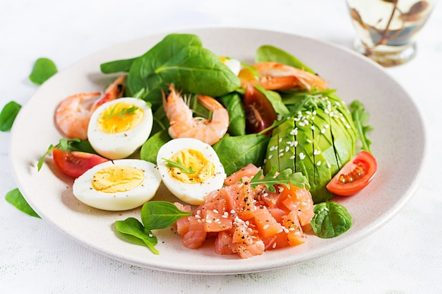 Colazione dietetica chetogenica. insalata di salmone salato con gamberi bolliti, gamberi, pomodori, spinaci, uova e avocado.