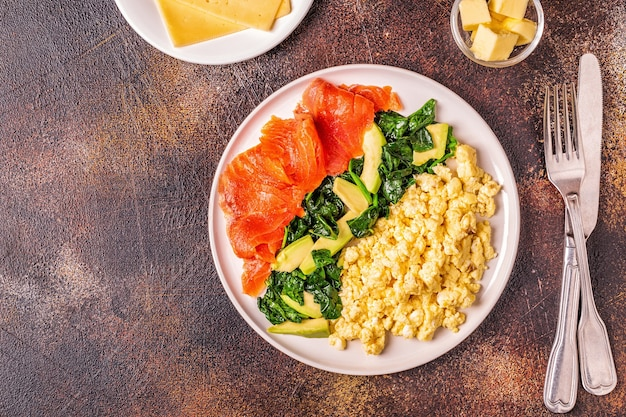 Colazione dietetica chetogenica, uova strapazzate, salmone, avocado, spinaci, vista dall'alto.