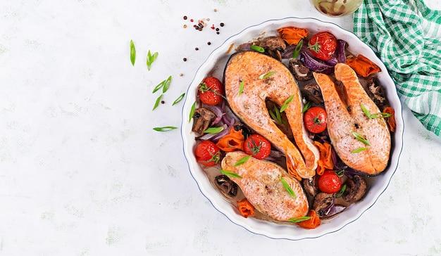 Cena chetogenica. trancio di salmone al forno con pomodori, funghi e cipolle rosse. menu dietetico cheto / paleo. vista dall'alto, in alto