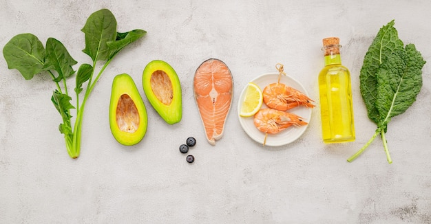 Concetto di dieta chetogenica a basso contenuto di carboidrati. ingredienti per la selezione di cibi sani impostati su sfondo bianco di cemento.
