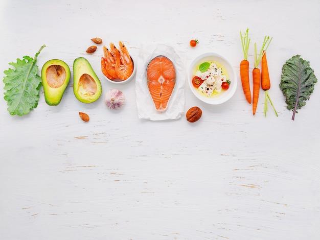 Concetto di dieta chetogenica a basso contenuto di carboidrati. ingredienti per la selezione di cibi sani impostati su fondo di legno bianco.