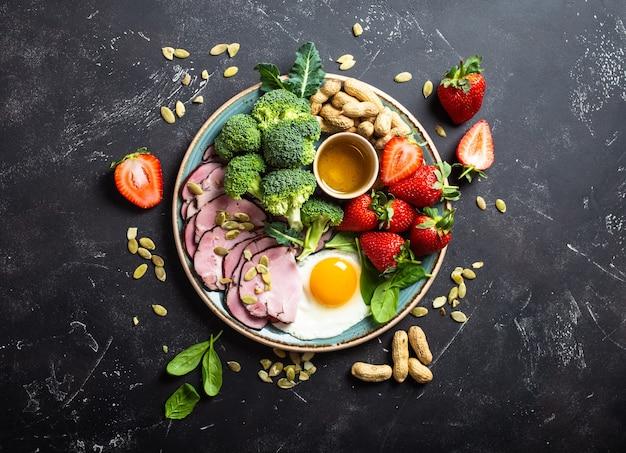 Concetto di dieta chetogenica a basso contenuto di carboidrati, vista dall'alto. piatto su fondo nero di pietra con alimenti cheto: uova, carne, olio d'oliva, broccoli, bacche, noci, semi, spinaci. grassi sani, alimentazione pulita per dimagrire
