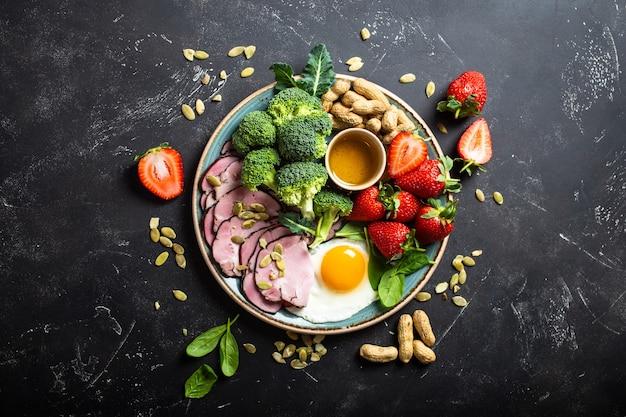 Vista dall'alto del concetto di dieta chetogenica a basso contenuto di carboidrati piastra su sfondo nero di pietra con alimenti cheto