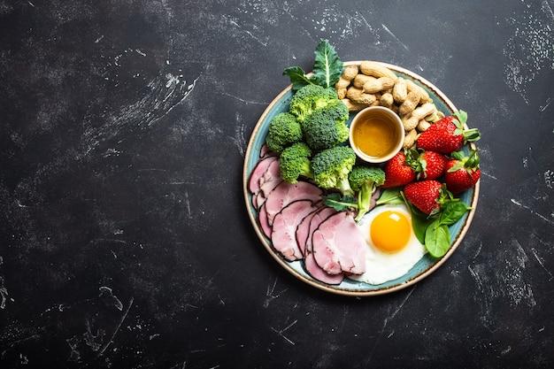 Dieta chetogenica a basso contenuto di carboidrati, vista dall'alto, spazio per il testo. piatto su fondo nero di pietra con alimenti cheto: uova, carne, olio d'oliva, broccoli, bacche, noci, semi. grassi sani, alimentazione pulita per dimagrire
