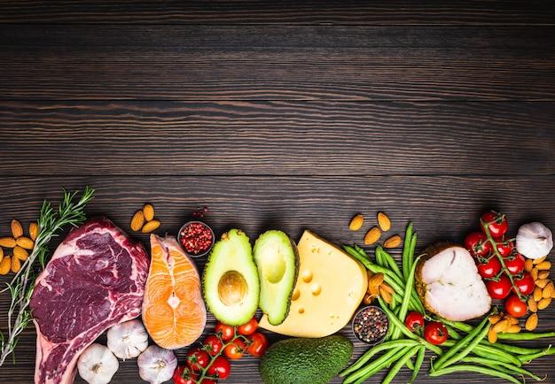 Ingredienti chetogenici a basso contenuto di carboidrati per una sana dieta dimagrante, vista dall'alto, copia spazio. alimenti cheto su fondo di legno: carne, pesce, avocado, formaggio, verdure, noci. mangiare sano, grassi sani
