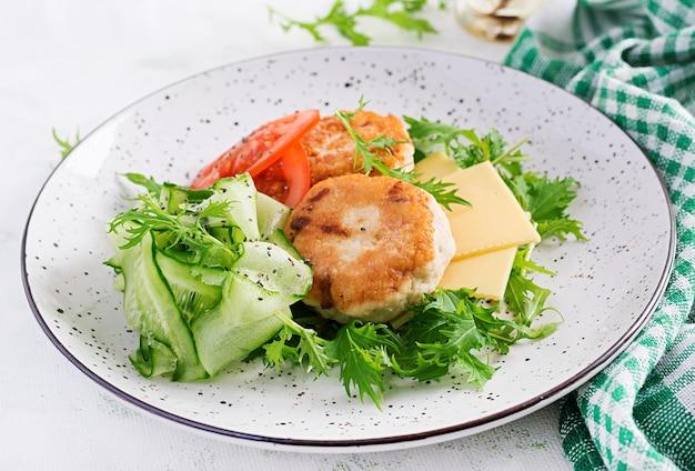 Pranzo chetogenico. hamburger di pollo con insalata di pomodori, cetrioli, formaggio e rucola senza panino