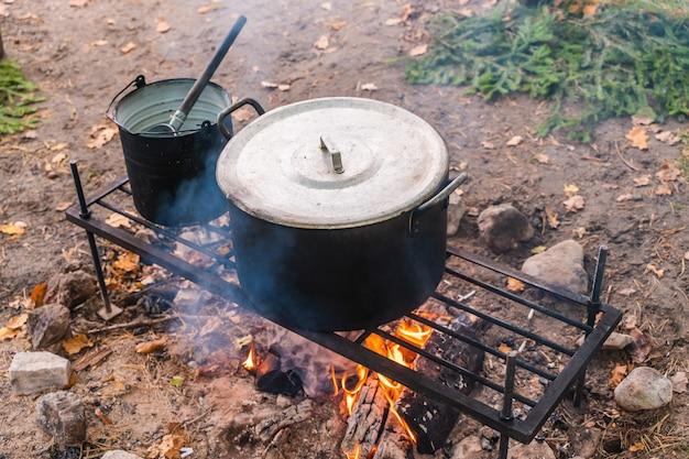 Bollitore sul fuoco. cucinare il cibo in natura. concetto di campeggio, viaggio e turismo