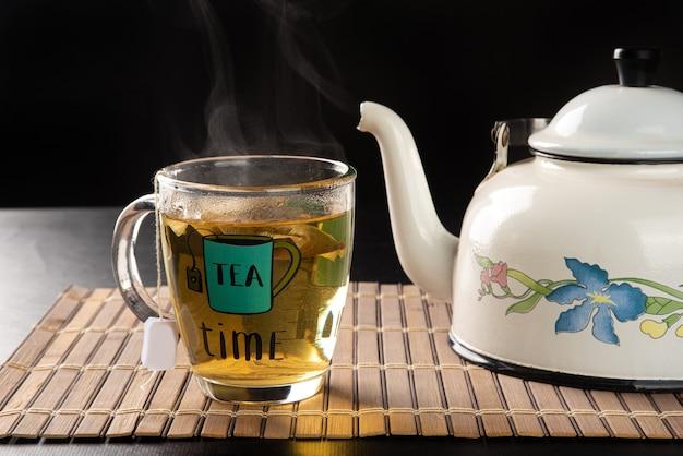 Bollitore e tazza di tè, entrambi uscenti dal fumo su una stuoia di legno