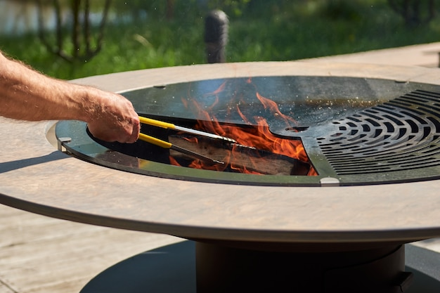 Bollitore per barbecue con griglia in ghisa con fiamme tavolo rotondo piano cottura hot bbq sul cortile