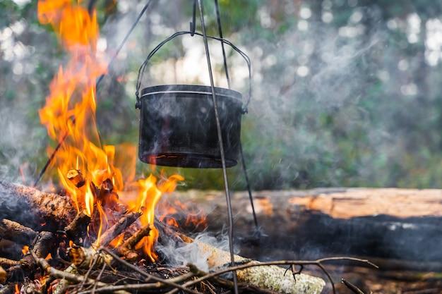 Bollitore appeso sopra il fuoco. cottura del cibo a fuoco in natura. viaggiare, concetto di turismo. foto d'archivio