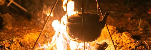 Il bollitore è sul fuoco durante la notte. falò con una fiamma ardente nel buio. striscione
