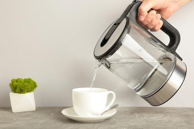 Bollitore versando acqua bollente in una tazza su sfondo grigio. vista dall'alto.