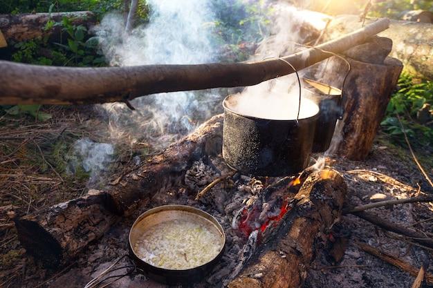 Bollitore sospeso sul fuoco da campo. escursioni in montagna