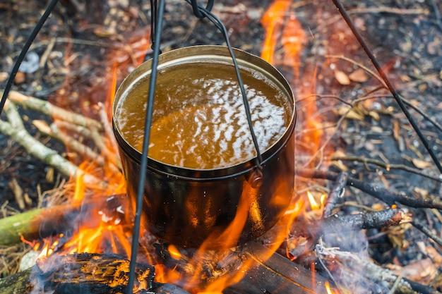 Bollitore con acqua sospesa sul fuoco. cottura del cibo a fuoco in natura. viaggiare, concetto di turismo. foto d'archivio