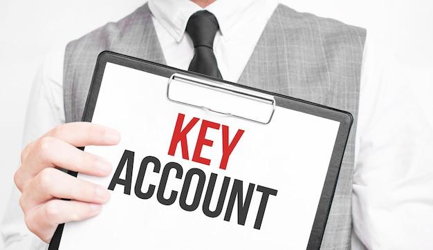 Iscrizione conto chiave su un taccuino nelle mani di un uomo d'affari su uno sfondo grigio