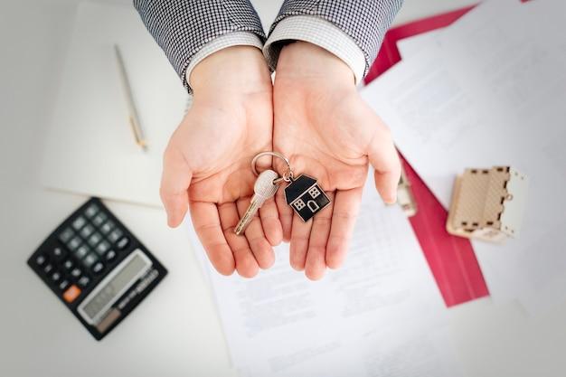 Chiave sulle mani di agente immobiliare