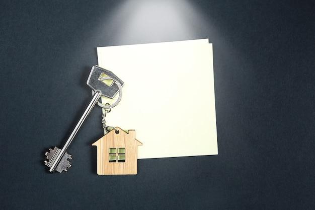 Chiave per la casa su un tavolo nero con un foglio quadrato per le note.