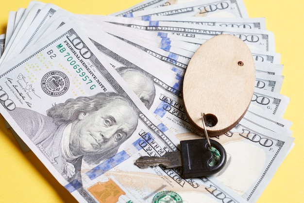 Chiave su un portachiavi che giace su banconote da un dollaro