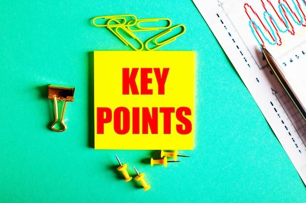 Punti chiave è scritto in rosso su un adesivo giallo su sfondo verde vicino al grafico e alla matita