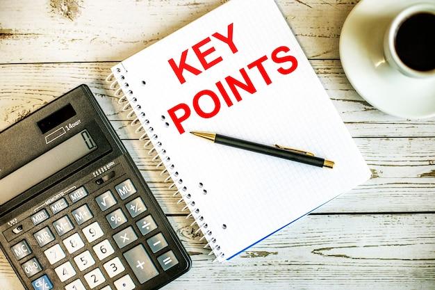 Punti chiave scritti su carta bianca vicino a caffè e calcolatrice su un tavolo in legno chiaro