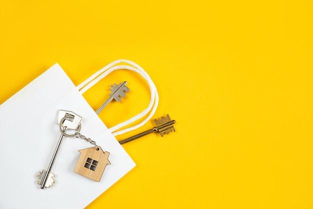 Portachiavi della casa in legno con chiave su una parete gialla in un sacchetto di carta bianca.