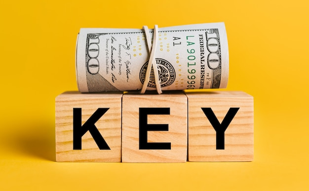 Chiave con soldi su un muro giallo