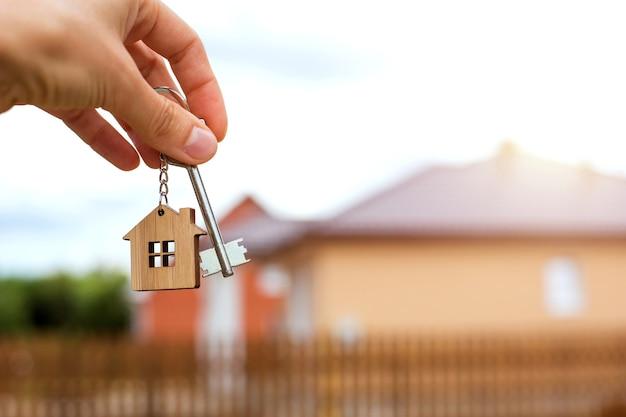 Chiave e portachiavi in legno a forma di casa in mano