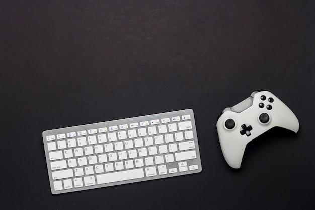 Tastiera e gamepad su uno sfondo nero. il concetto di gioco su pc, giochi, console. vista piana, vista dall'alto.