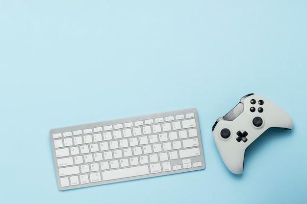 Tastiera e gamepad su uno sfondo blu. il concetto di giochi per computer, intrattenimento, giochi, tempo libero. vista piana, vista dall'alto