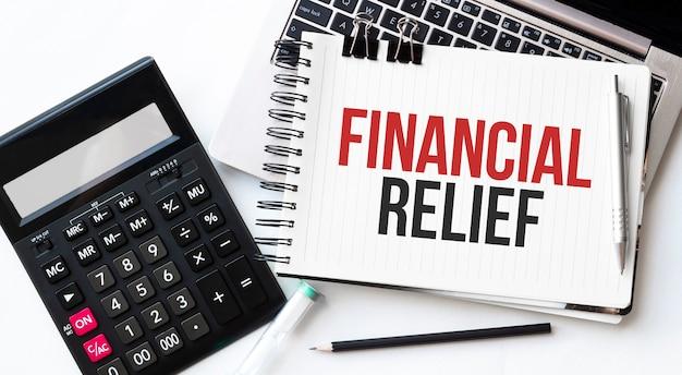 Tastiera del computer portatile, calcualtor, matita e blocco note con rilievo finanziario del testo