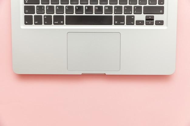Computer portatile tastiera isolato su sfondo scrivania rosa pastello. la moderna tecnologia dell'informazione e il software avanza. programmatore freelance di home office o concetto di spazio di lavoro di design