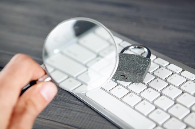 Tastiera, lente d'ingrandimento e lucchetto. concetto di ricerca di protezione. difese apprese. tavolo in legno grigio