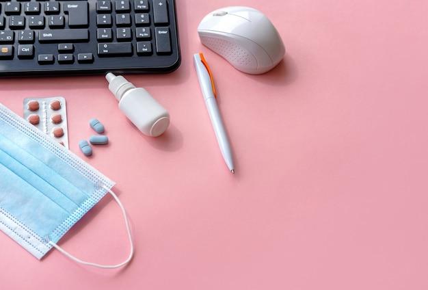 Tastiera, mascherina medica e pillole sul tavolo