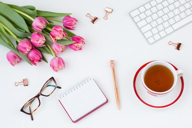 Tastiera, graffette, occhiali, taccuino, penna, tazza da tè e bouquet di tulipani rosa