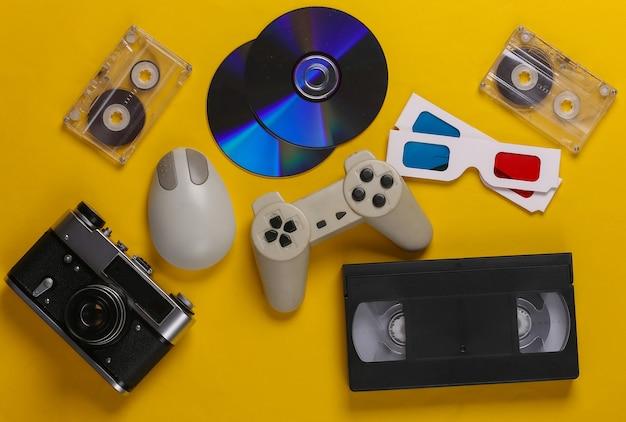 Tastiera, mouse per pc, compact disc, gamepad, occhiali anaglifi, audio e videocassetta, fotocamera su giallo