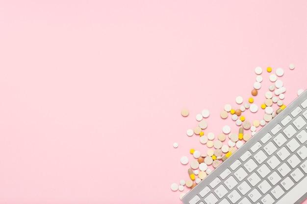 Tastiera e pillole su sfondo rosa. il concetto di ordinare e acquistare medicinali, vitamine e pillole su internet, un negozio online. vista piana, vista dall'alto.