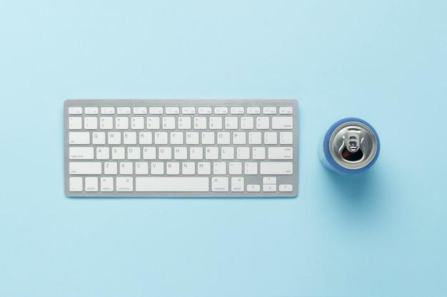 Tastiera e barattolo di latta con un drink, energy drink su sfondo blu. concetto di business, lavorare al computer, giocare a ps, film e programmi tv online. vista piana, vista dall'alto