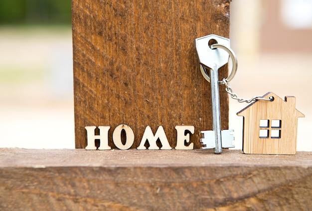 Portachiavi di figura in legno casa sul recinto con chiave
