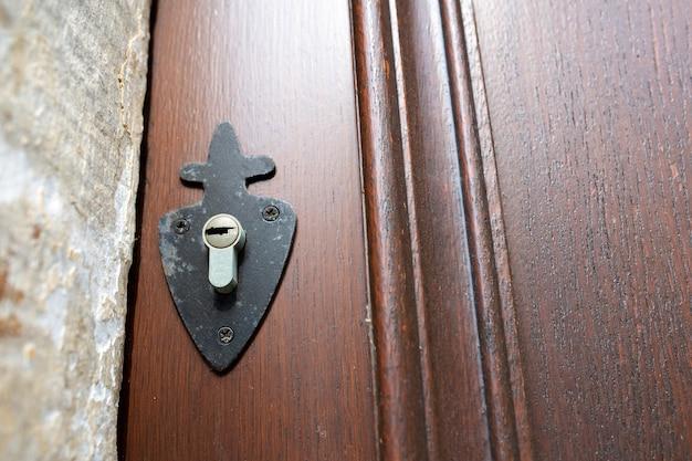 Buco della serratura su una porta intagliata marrone. spazio vuoto