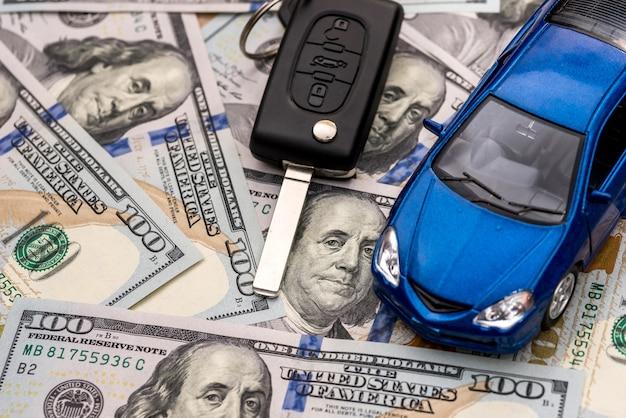 Chiavi della macchina e della macchina che giacciono su banconote da 100 dollari